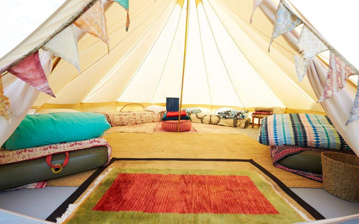 Glamping in a teepee tent pitched with rugs.