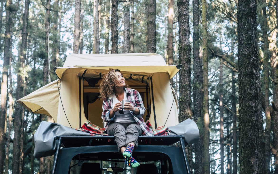 Happy cheerful beautiful people caucasian adult woman sit down on the roof of the car with tent in background and forest around