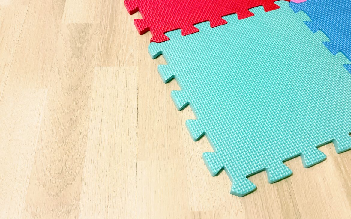 oft rubber mat composed of colored blocks intersected with each other on a wooden floor