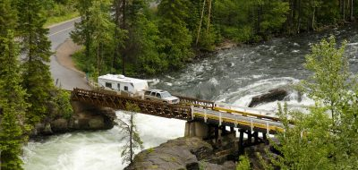 RV towing a fifth-wheel drives over a bridge