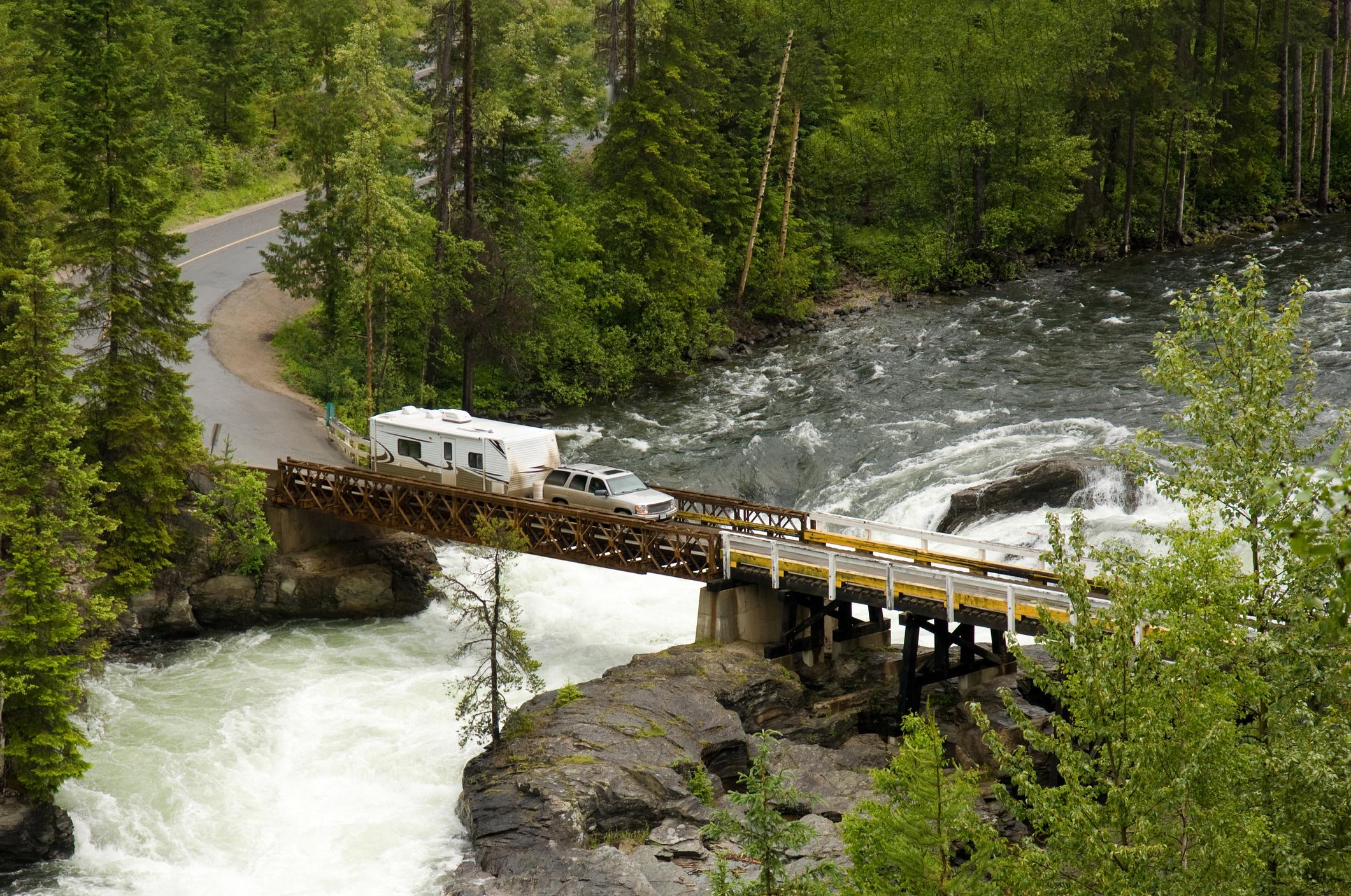 RV towing a fifth-wheel drives over a bridge