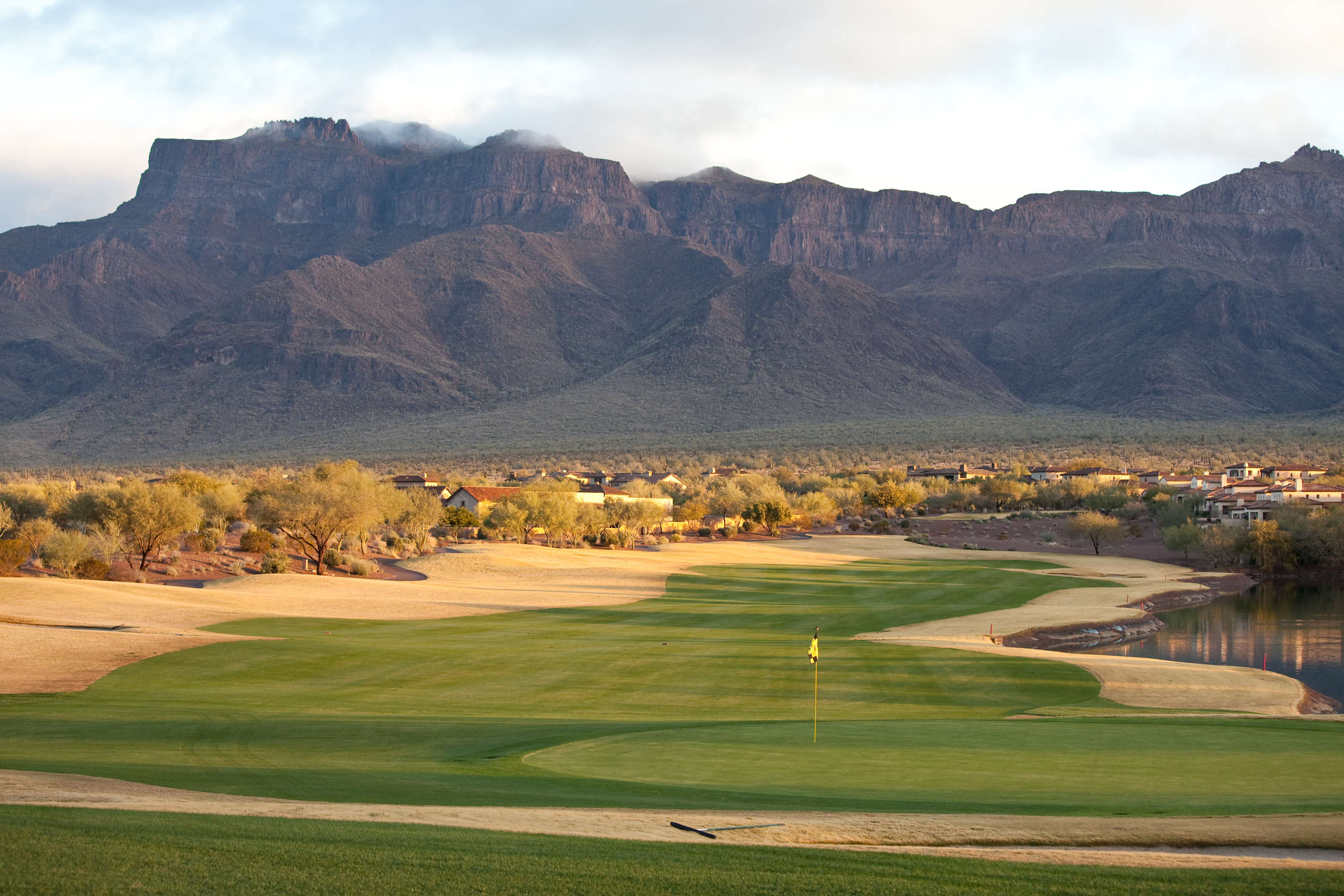A lush fairway framed by rugged mountains on the horizon.