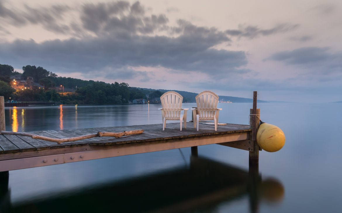 Two chairs sitting on a jetty at dusk, form a tranquil and idyllic scene at Lake Seneca, Finger Lakes in New York