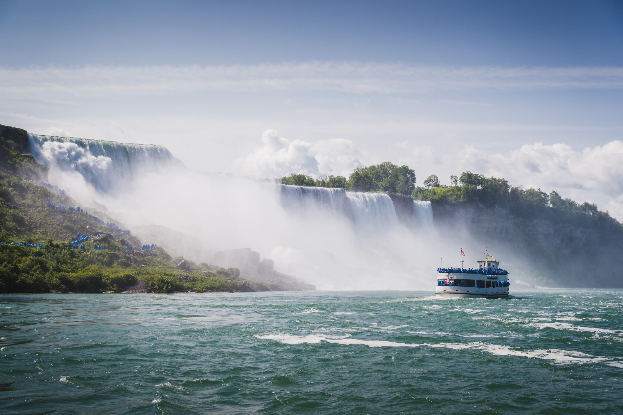 Perfect Family Vacation Spot — a tour boat chugs to the foot of niagara falls.