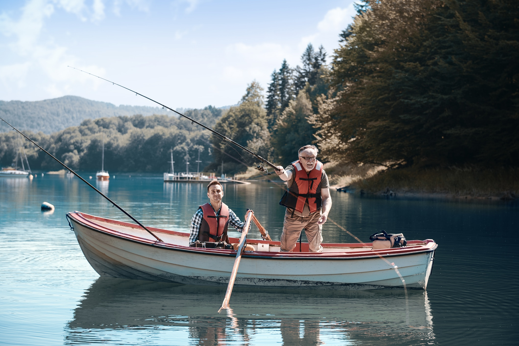 Senior man and 30-something guy in a row boat.