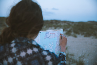 Woman reading map sitting on beach at Hatteras Island