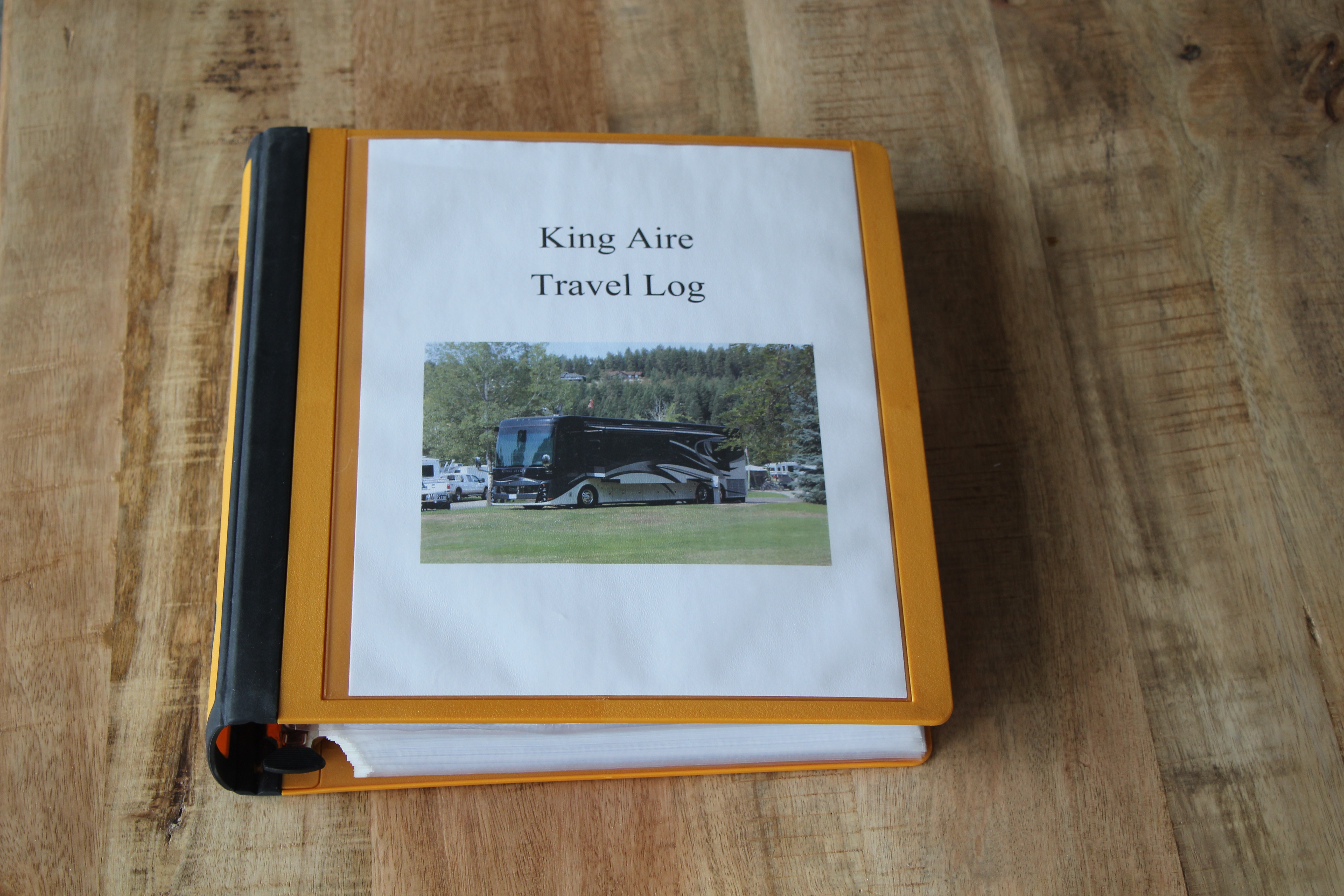 An RV log book in an orange binder.