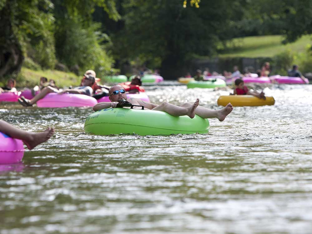 People drifting down a river in colorful inner tubes.