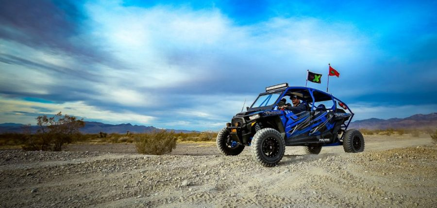 Visit Pahrump to hit the trails —an offroad vehicle races across a rugged landscape.
