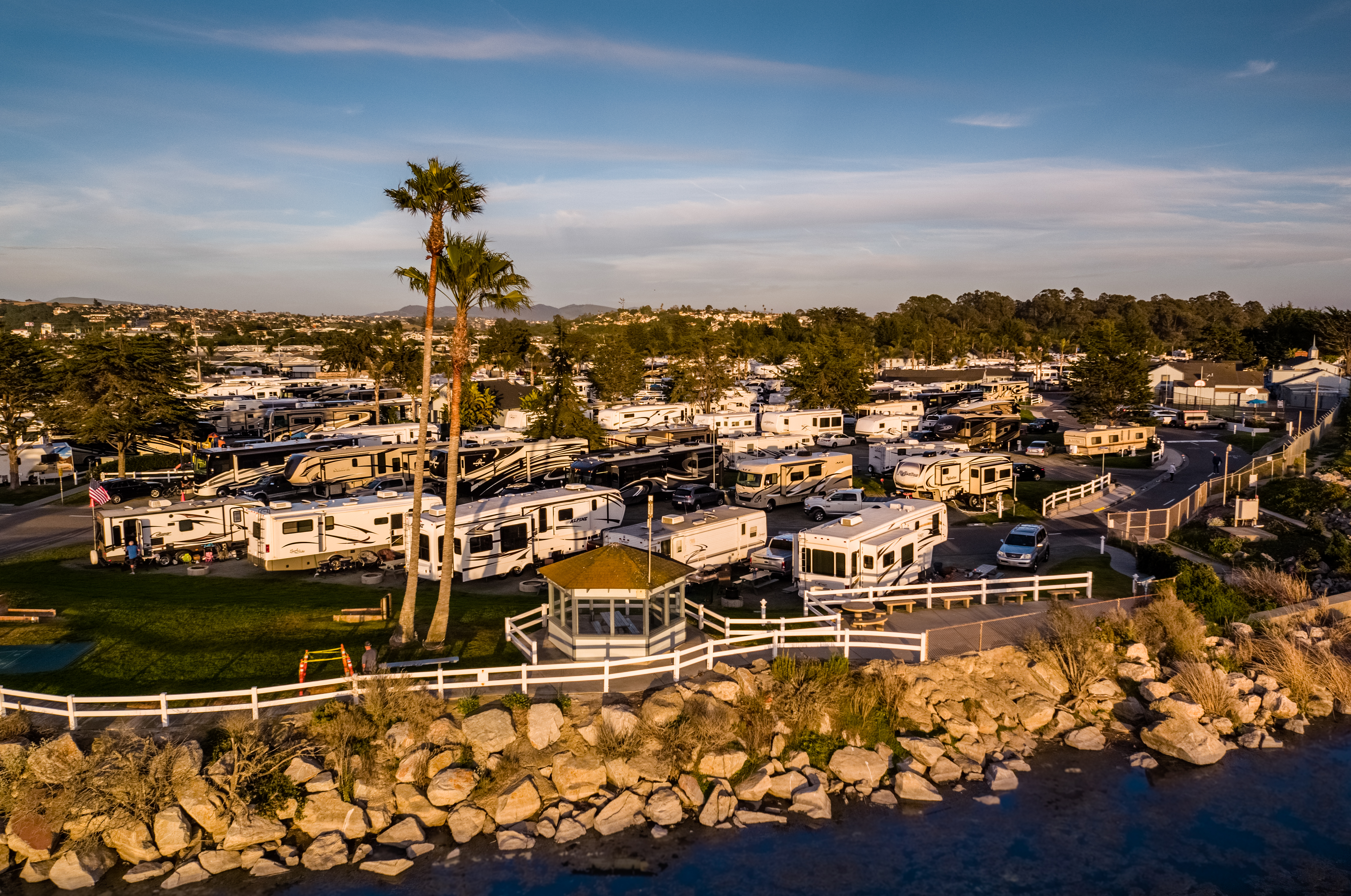 Aerial view of an RV park perched on a rocky bluff overlooking hte water.