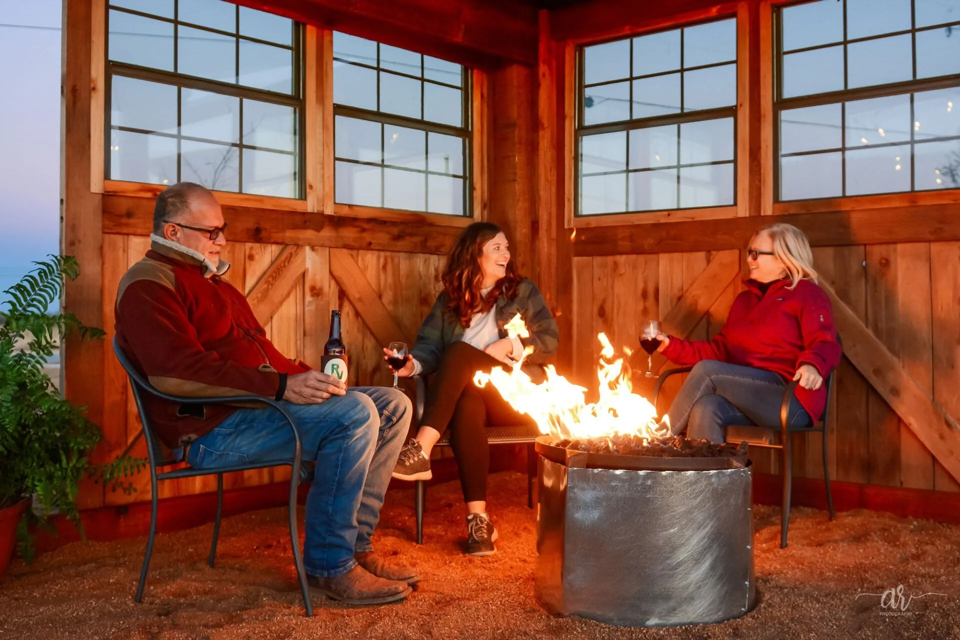 Three campers gathered around a fire in a enclosed space.