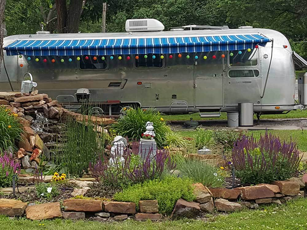 A silver bullet travel trailer amid a landscape of gnomges and rocks.