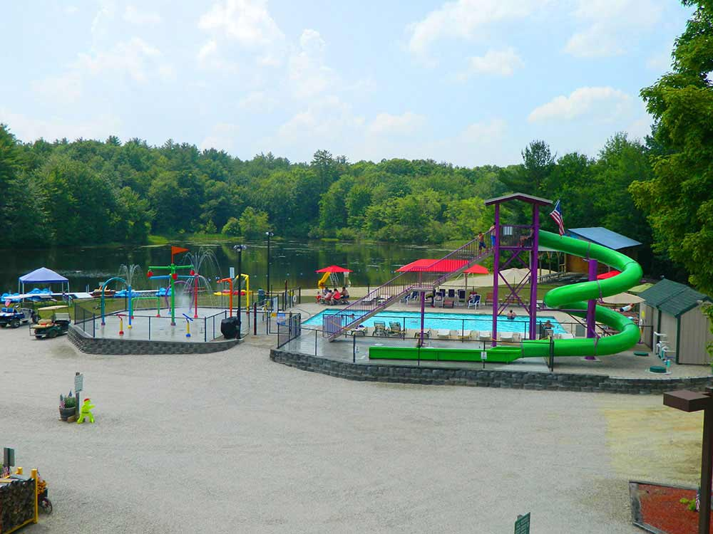 Water recreation equipment like slide and splash pad with lake in background.