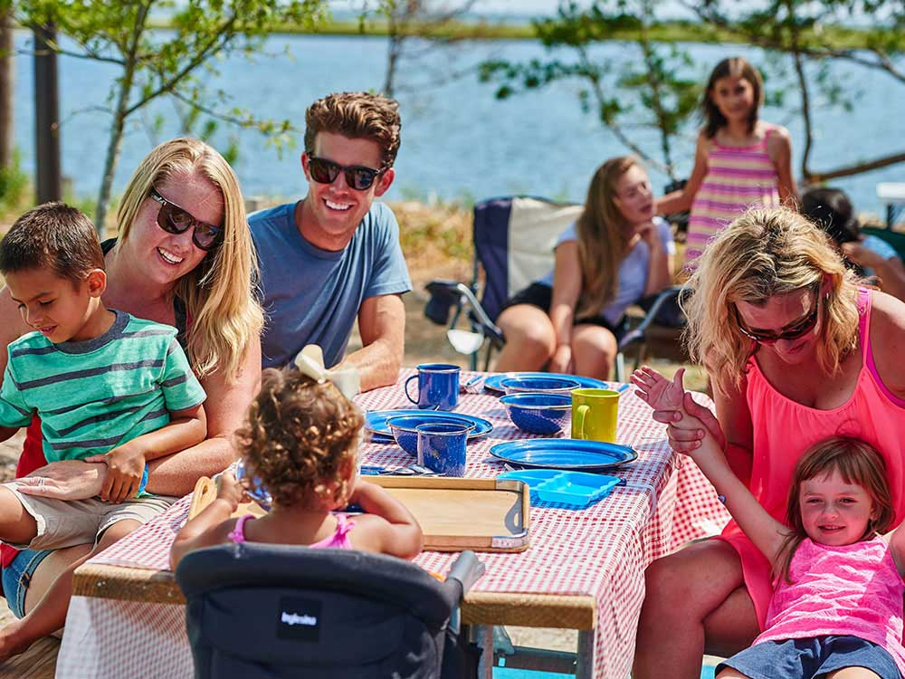 Family gathered around picnic table near lake.