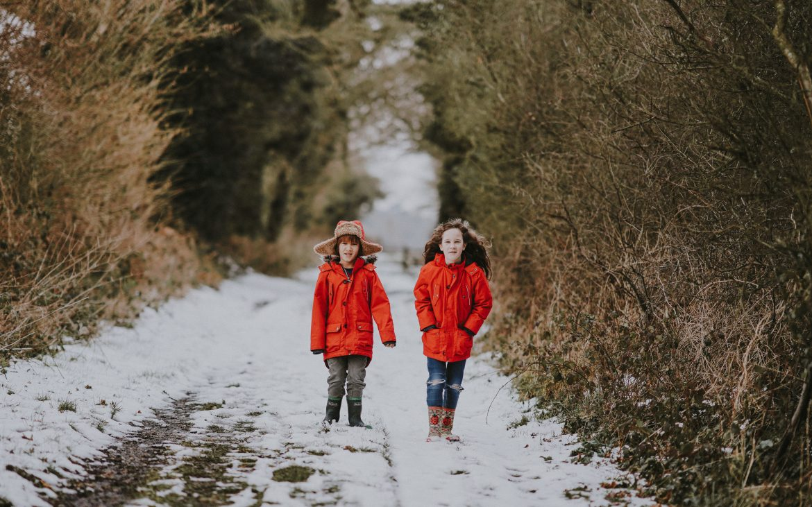 Two young girls walking outside on snowy path