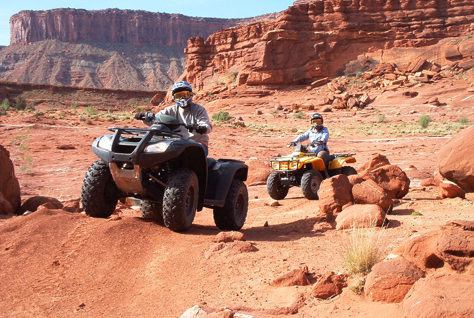 A pair of ATV riders follow a dirt trail through a rugged landscape.