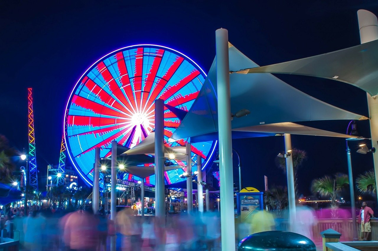 Colorful Ferris wheel spinning as blurred figures navigate the boardwalk.