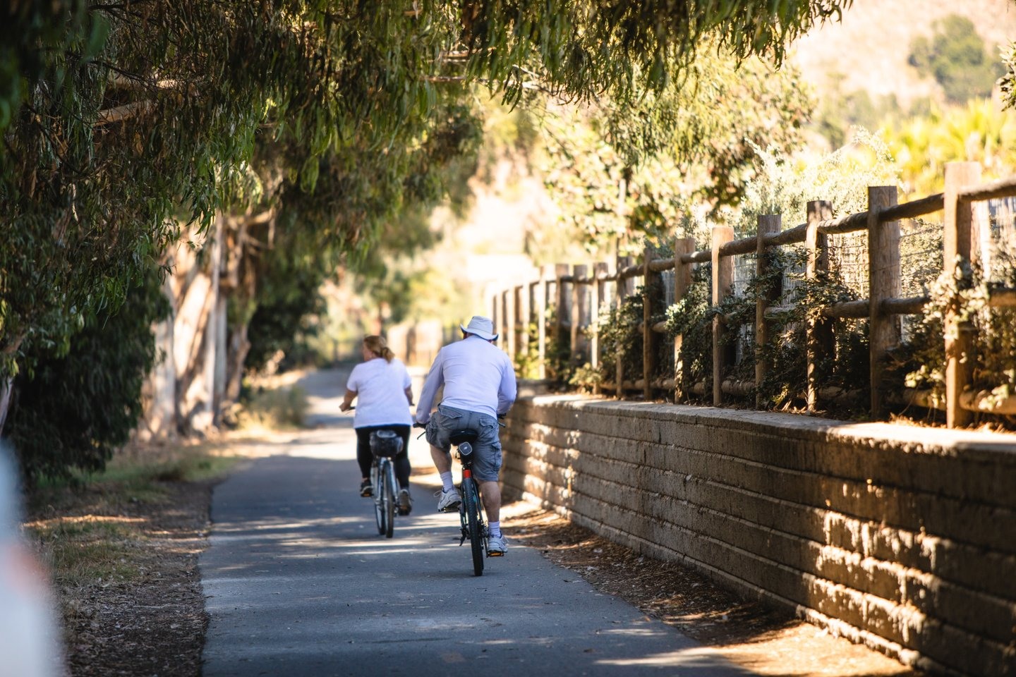 A pair of older bikers cruiser down a shaded bike path.