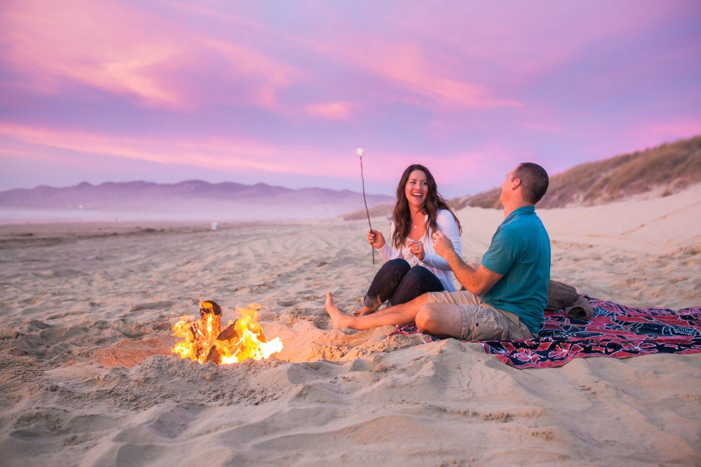 A couple laughs happily as they barbecue on a beach.