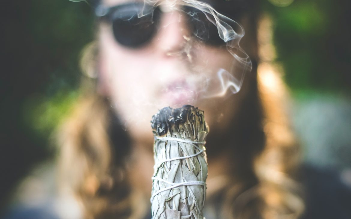 person blowing smoke from sage