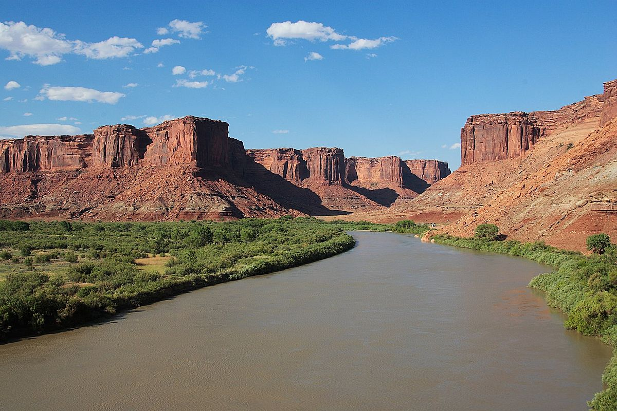 A river rolls through a rugged landscape of looming stone mesas.
