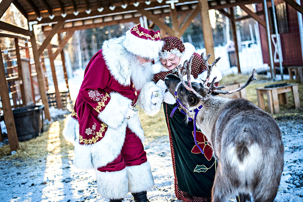 A senior man and woman dressed as Santa and Mrs. Claus with a deer.