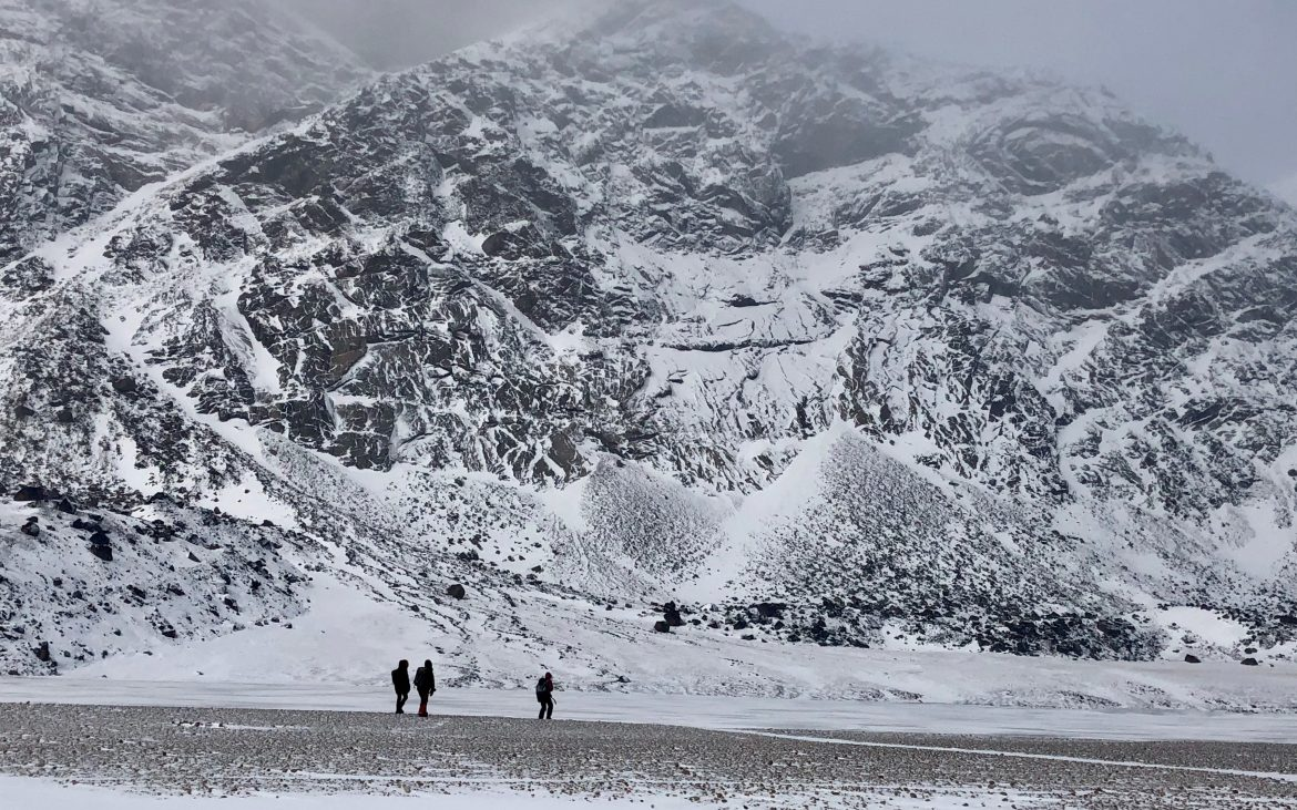 Three people walking among glaciers and mountains at Auyuittuq National Park