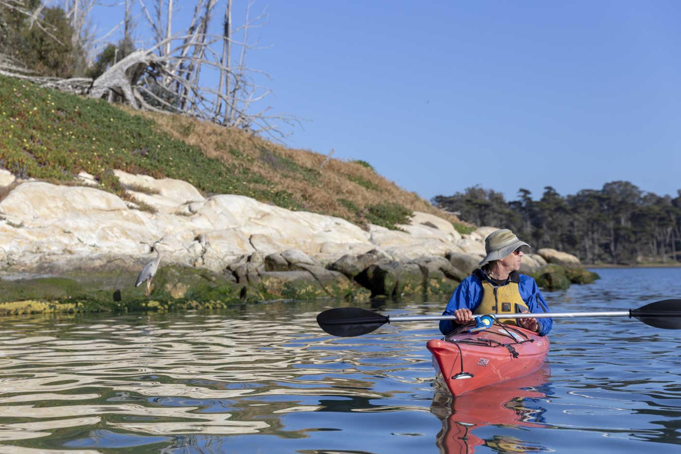 A man paddling a red kayak near a rocky shore.