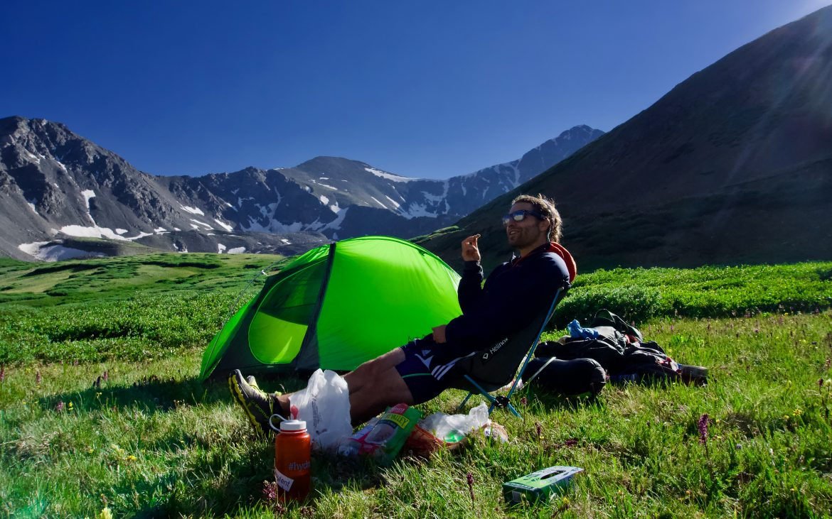 Man sitting in chair on grassy mountain next to green tent