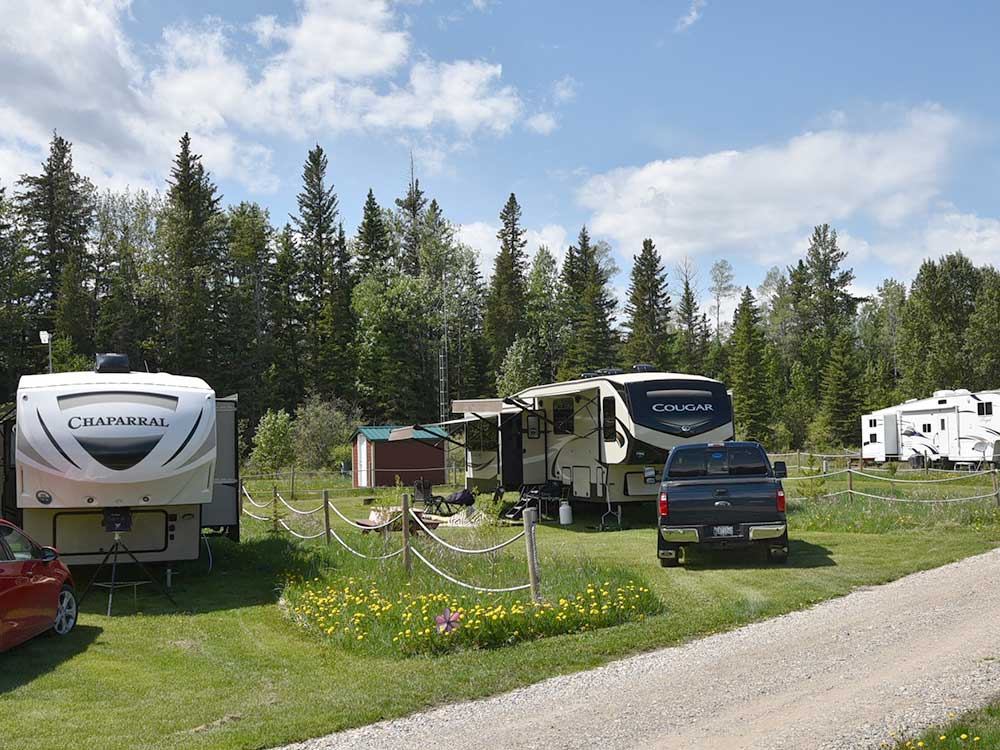 Fifth wheels parked on grassy sites with treeline in background.