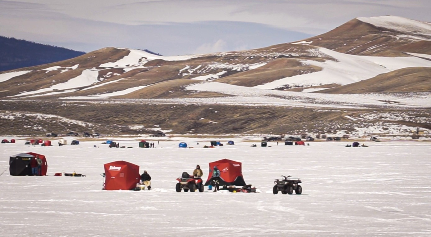 Several ice fishing enthusiasts on white ice.