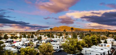 RV park sprawls under a blue sky with rugged mountains in background.