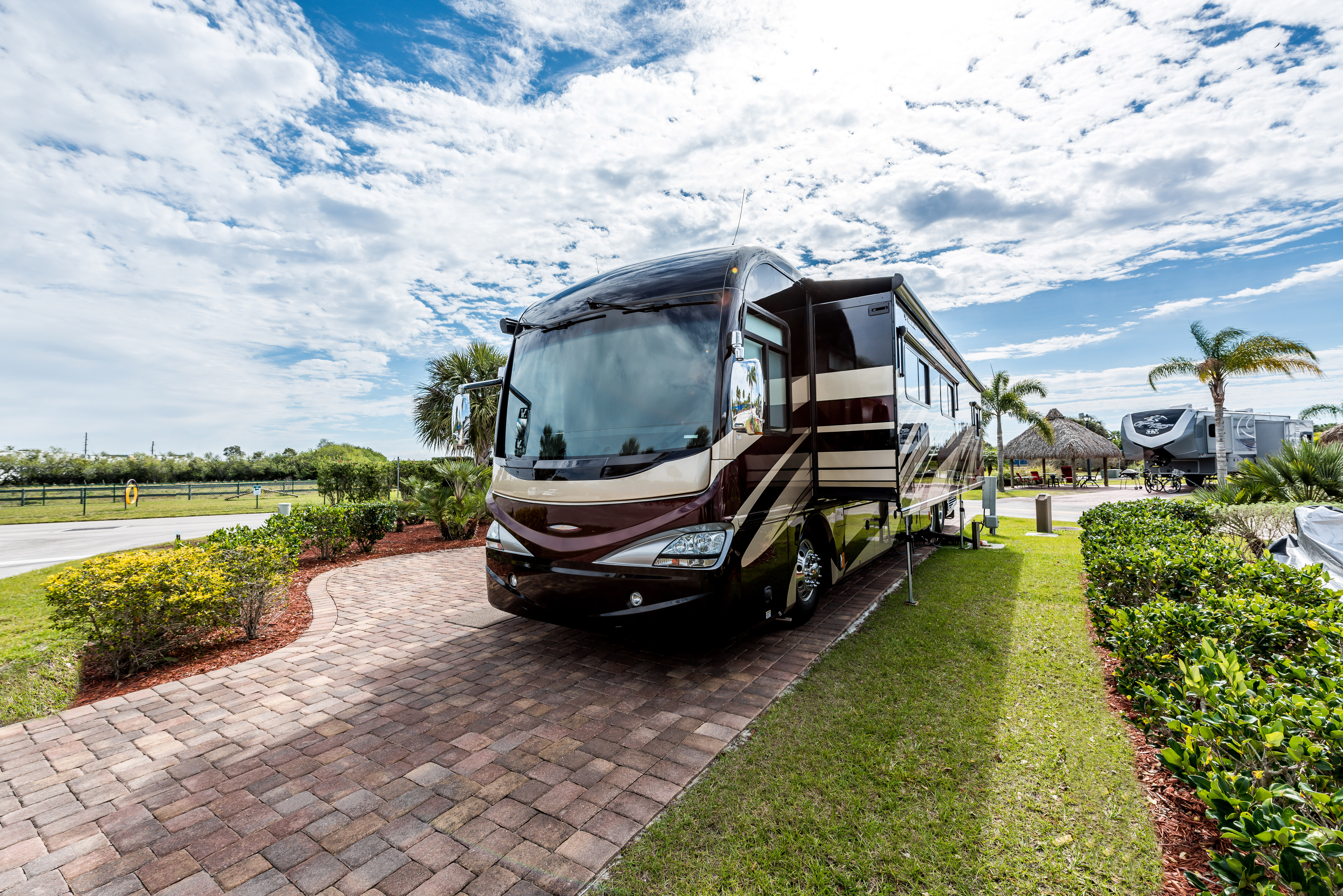 Florida fun to your weekends —Motorhome parked on a brick pad flanked by lush grass.
