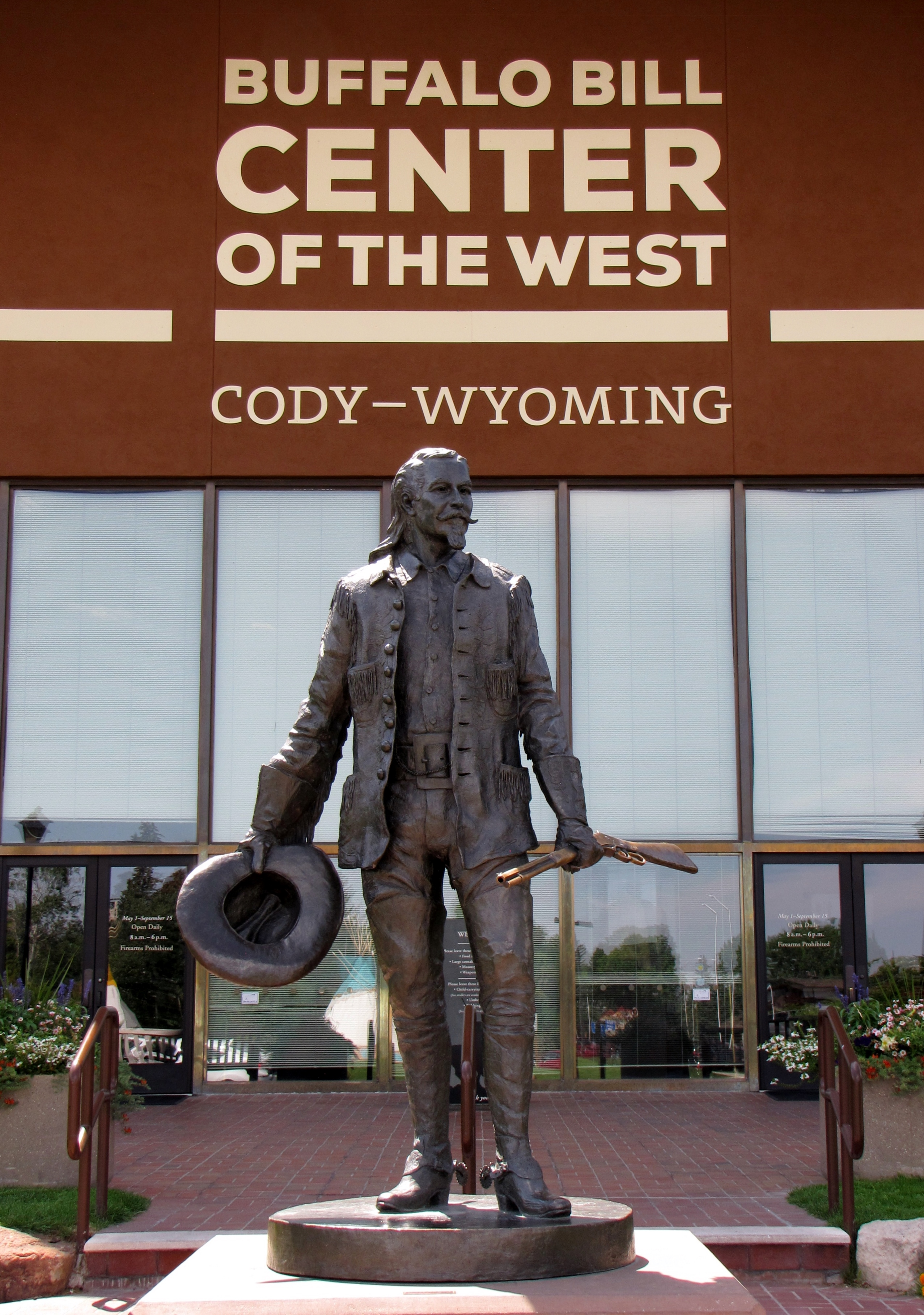 Bronze statue of man holding rifle and his cowboy hat.