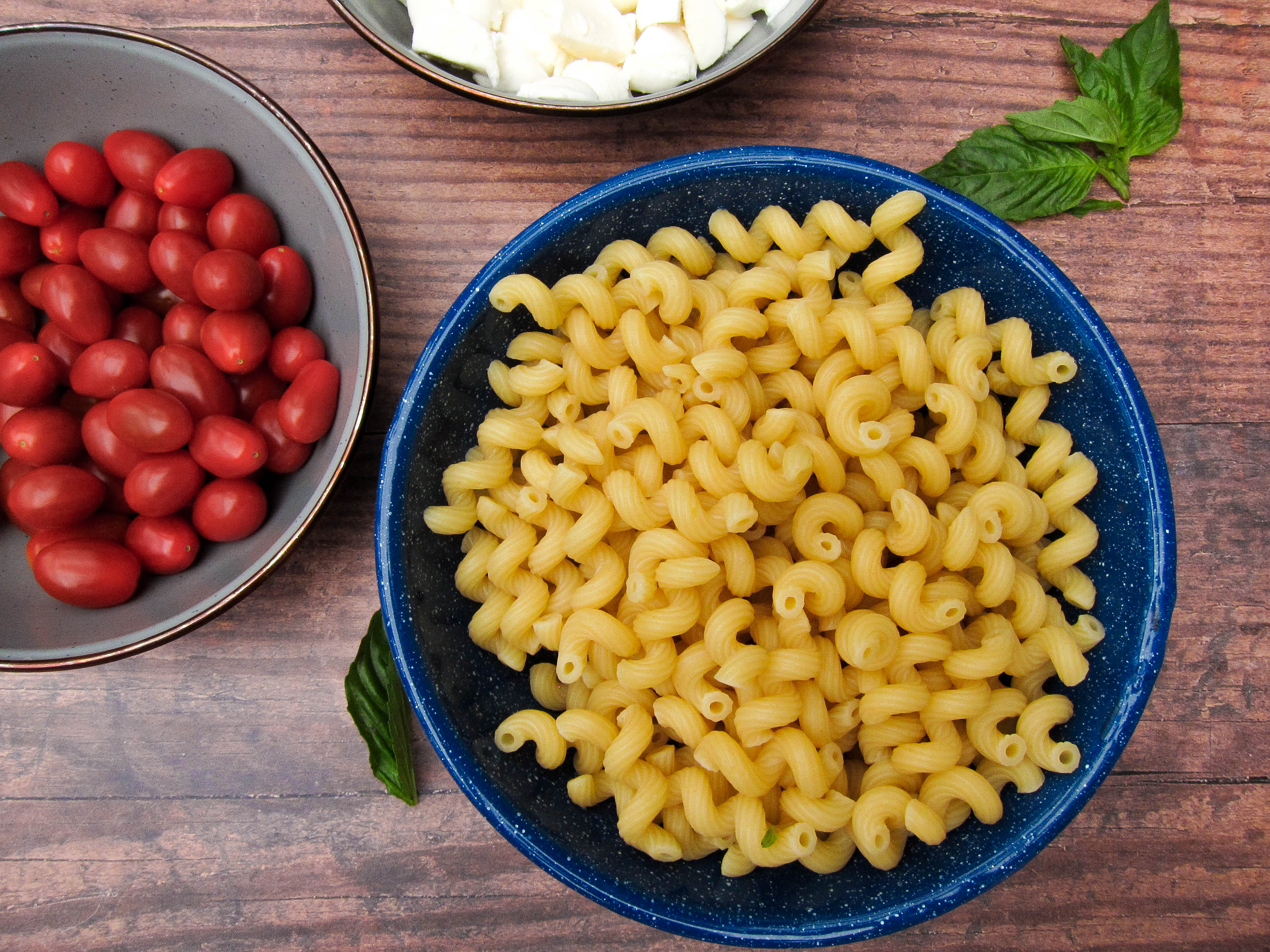Blue bowl of pasta salad near bowl of tomatoes.