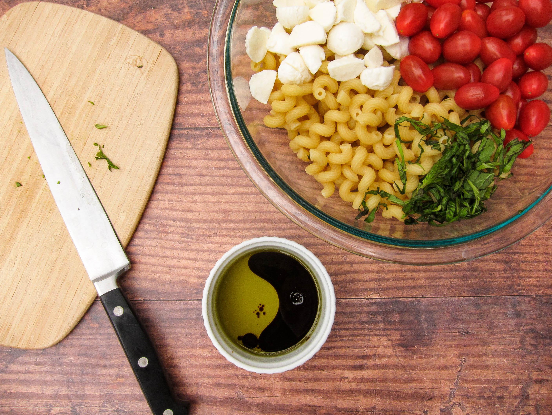 Knife, cutting board, vinnegar and bowl of salad