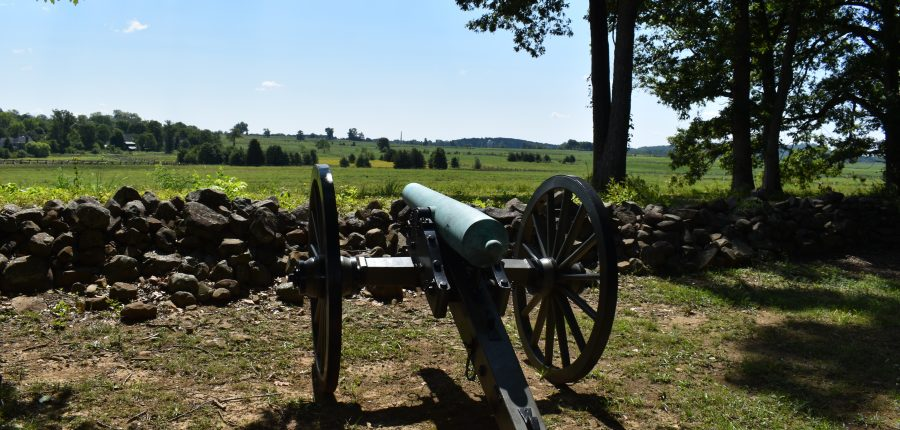 Historic Gettysburg — Cannon pointed at horizon under a clear blue sky.