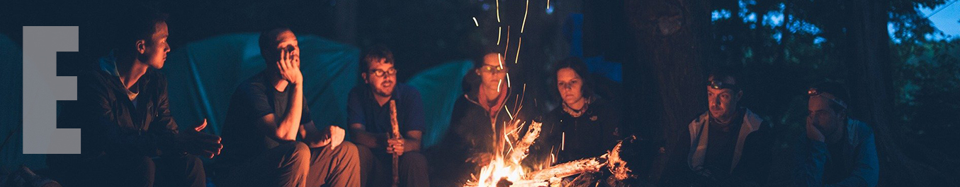 A group gathered around a campfire that throws up sparks.