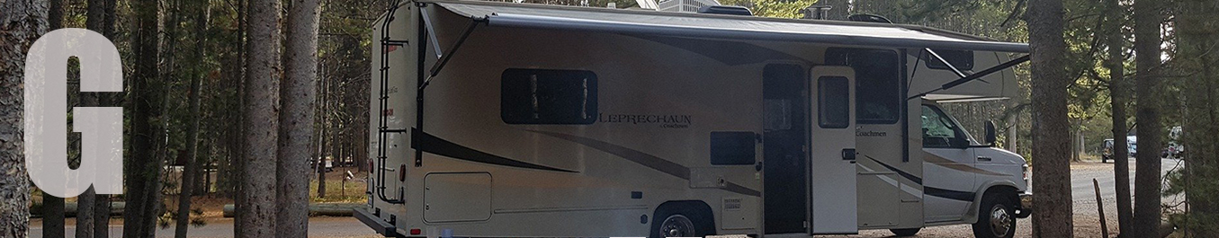 An RV with awning unfurled and door open.
