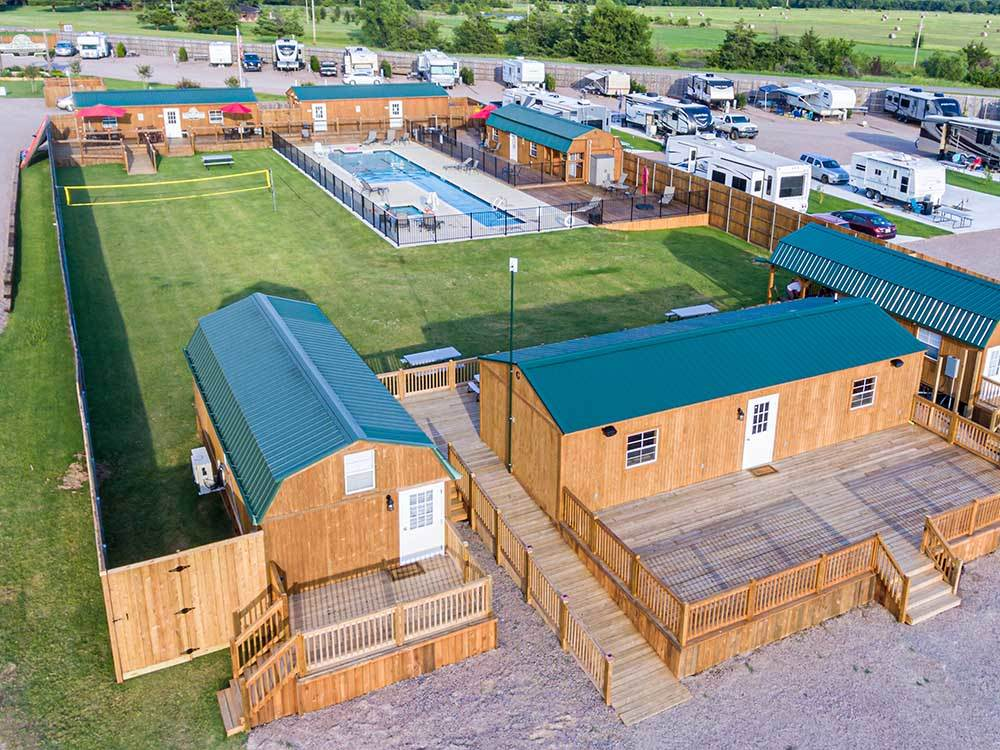 Aerial shot of pool, yard and buildings at the core of a neat RV resort.