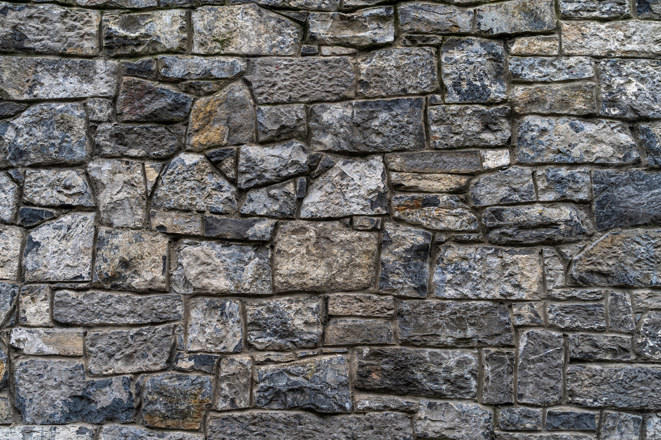 Rough-hewn bricks assembled to form a solid rock wall.