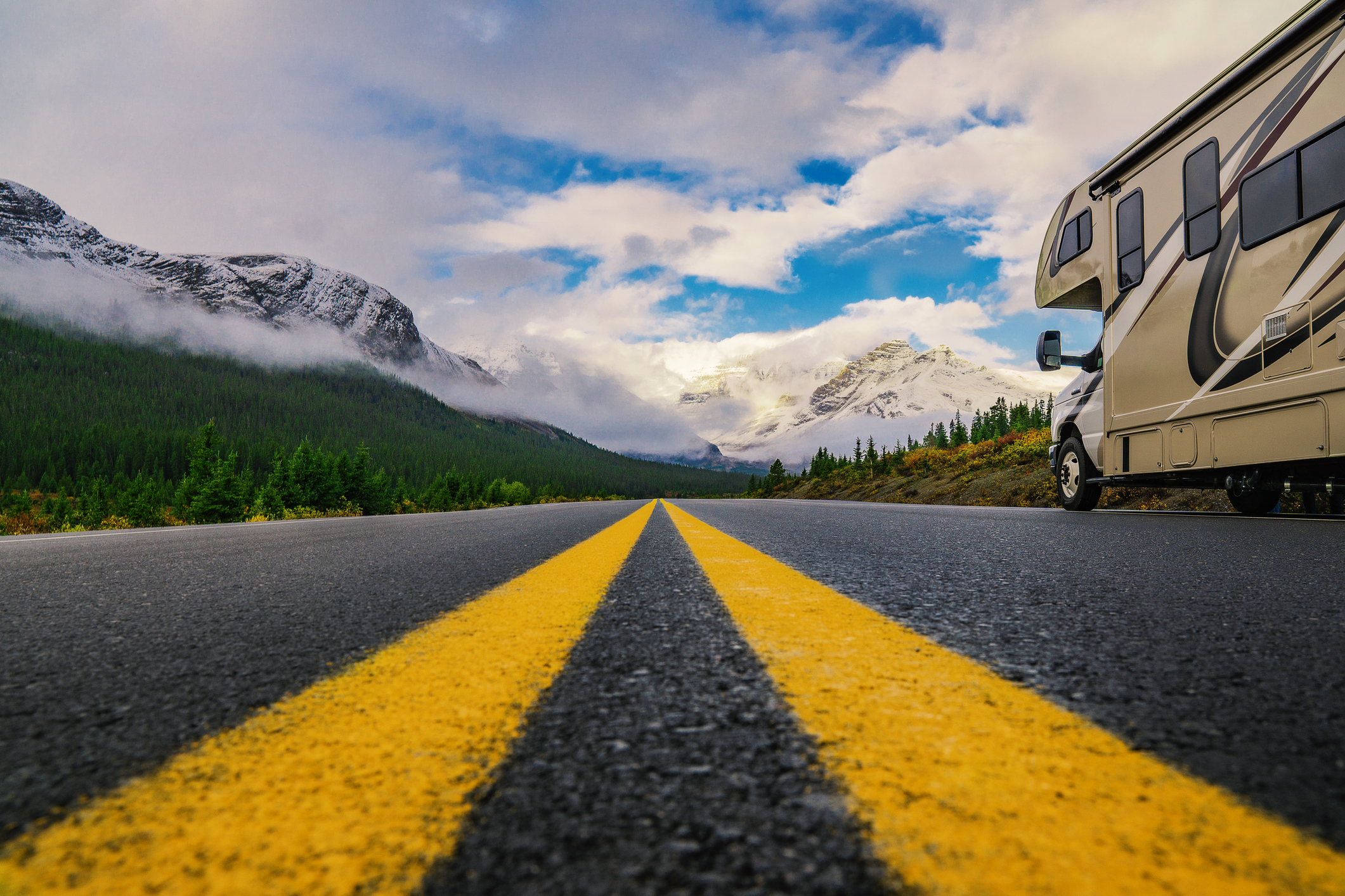 A motorhome on a highway with majestic mountains in the background.