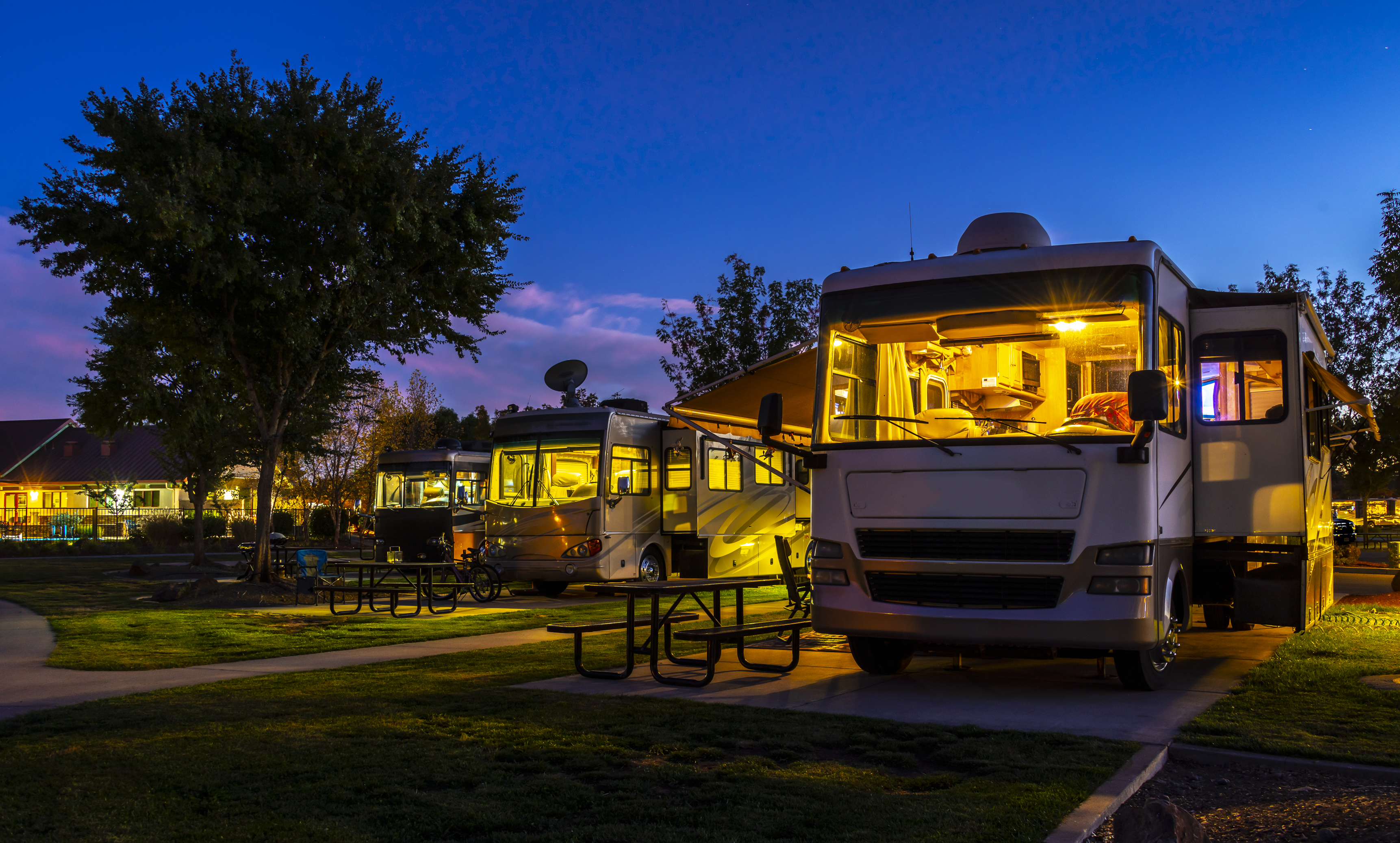 Class A motorhomes illuminated with windows uncovered.