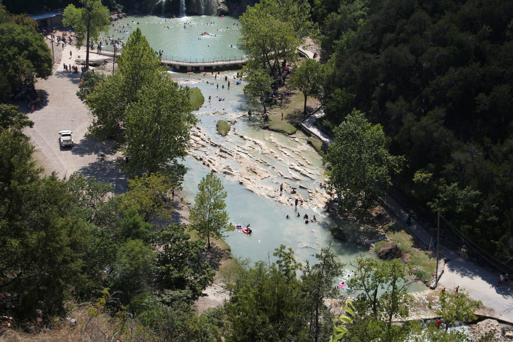 Aerial view of waterfalls and people playing at the food of the cascades