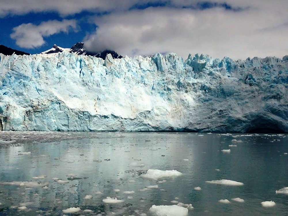 A glacier looms over placid water.