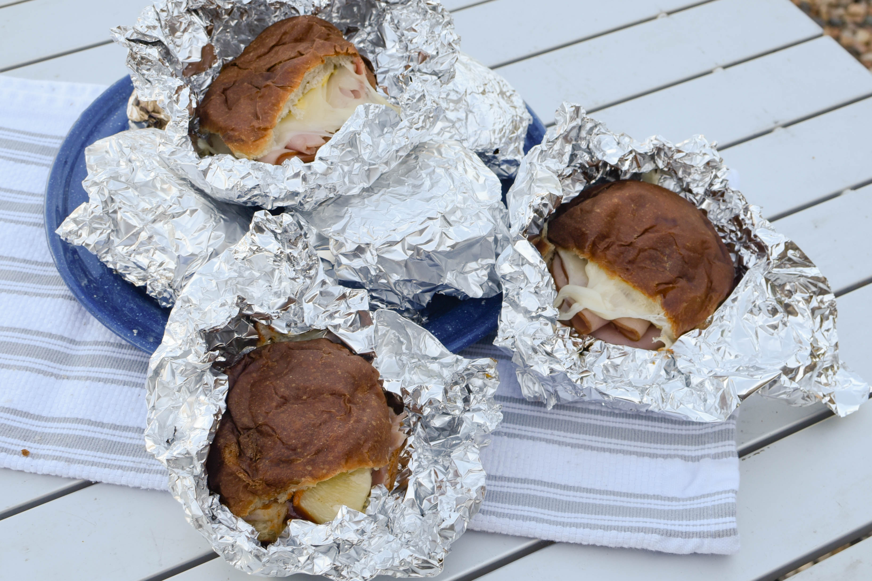 Three ham sandwiches with gooey cheese wrapped in foil.