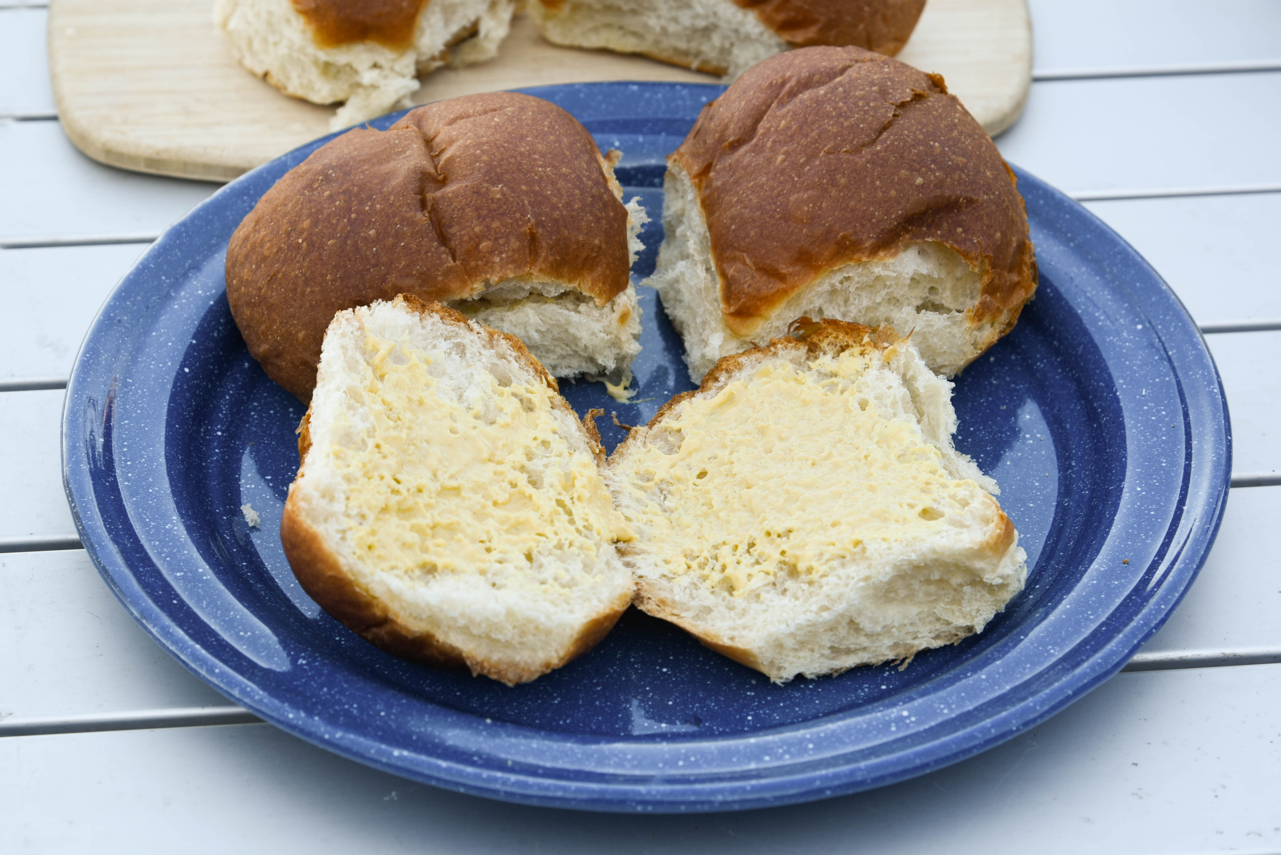 Hawaiian rolls cut in half with both sides buttered.