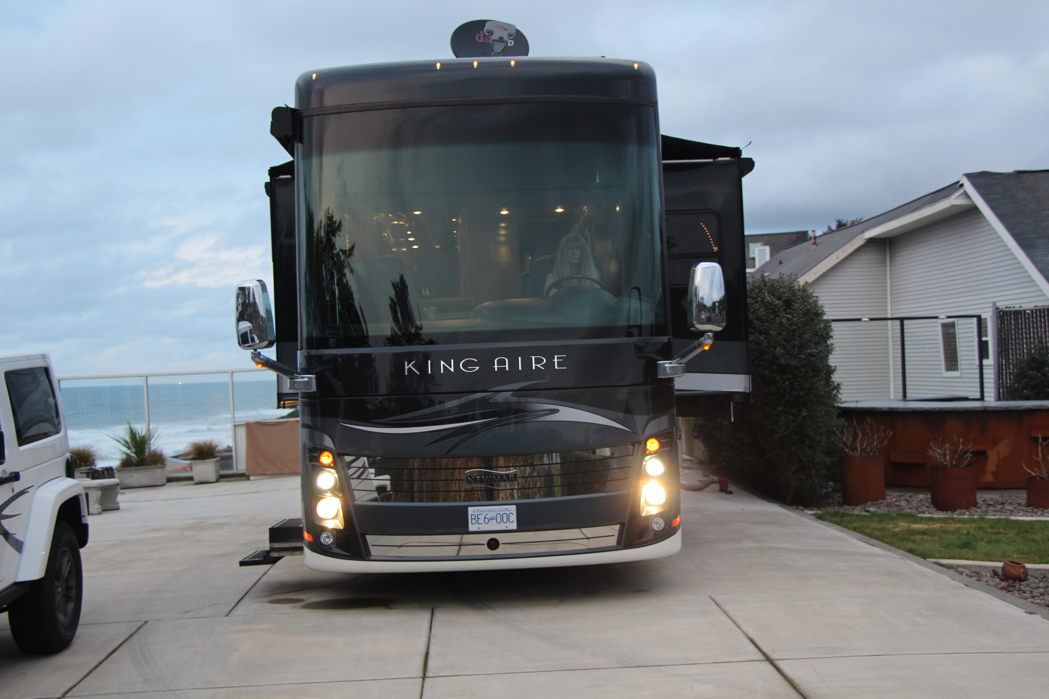 Big Class A motorhome on a home driveway with lights on.