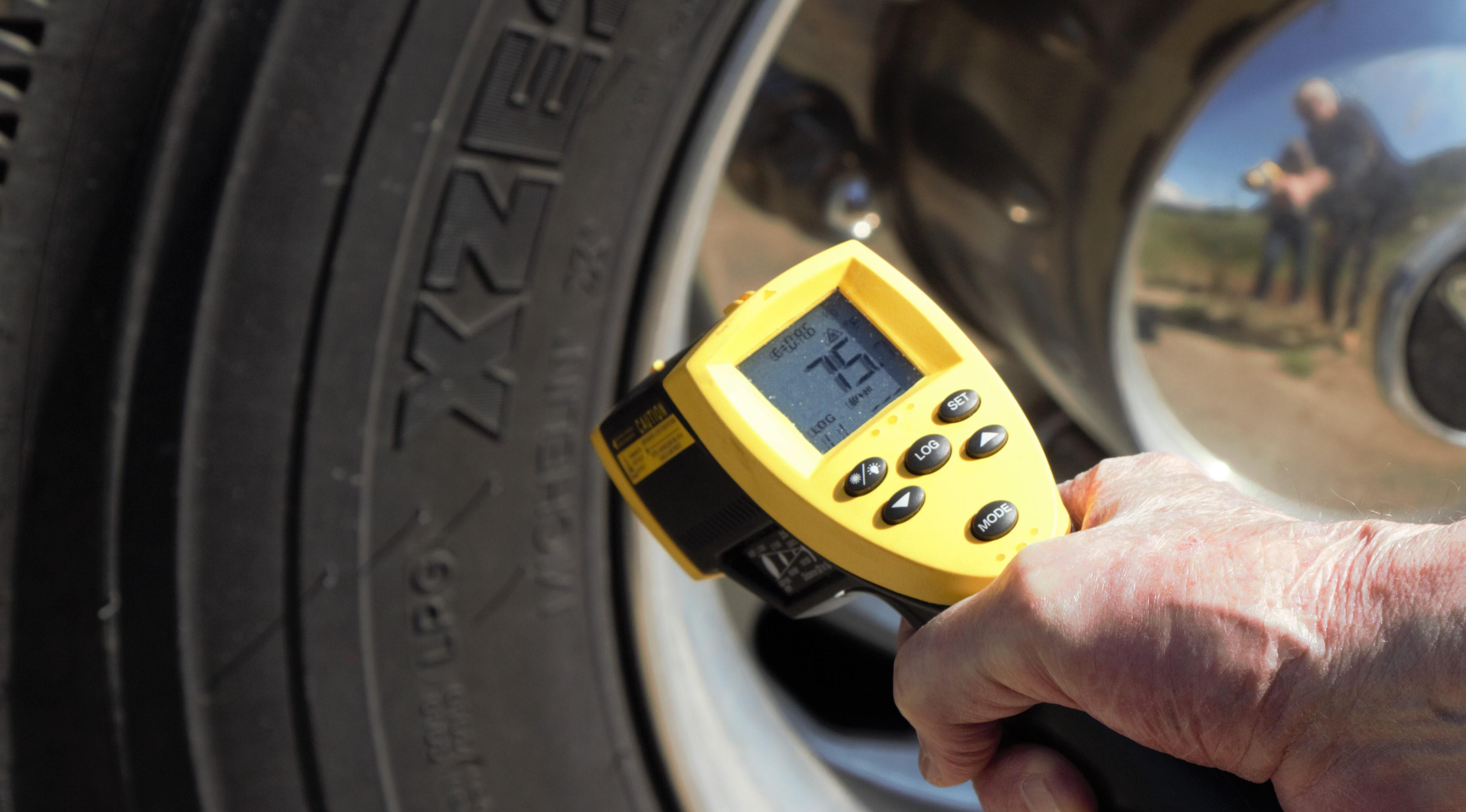 A hand aims an infrared temperature gun at a tire.