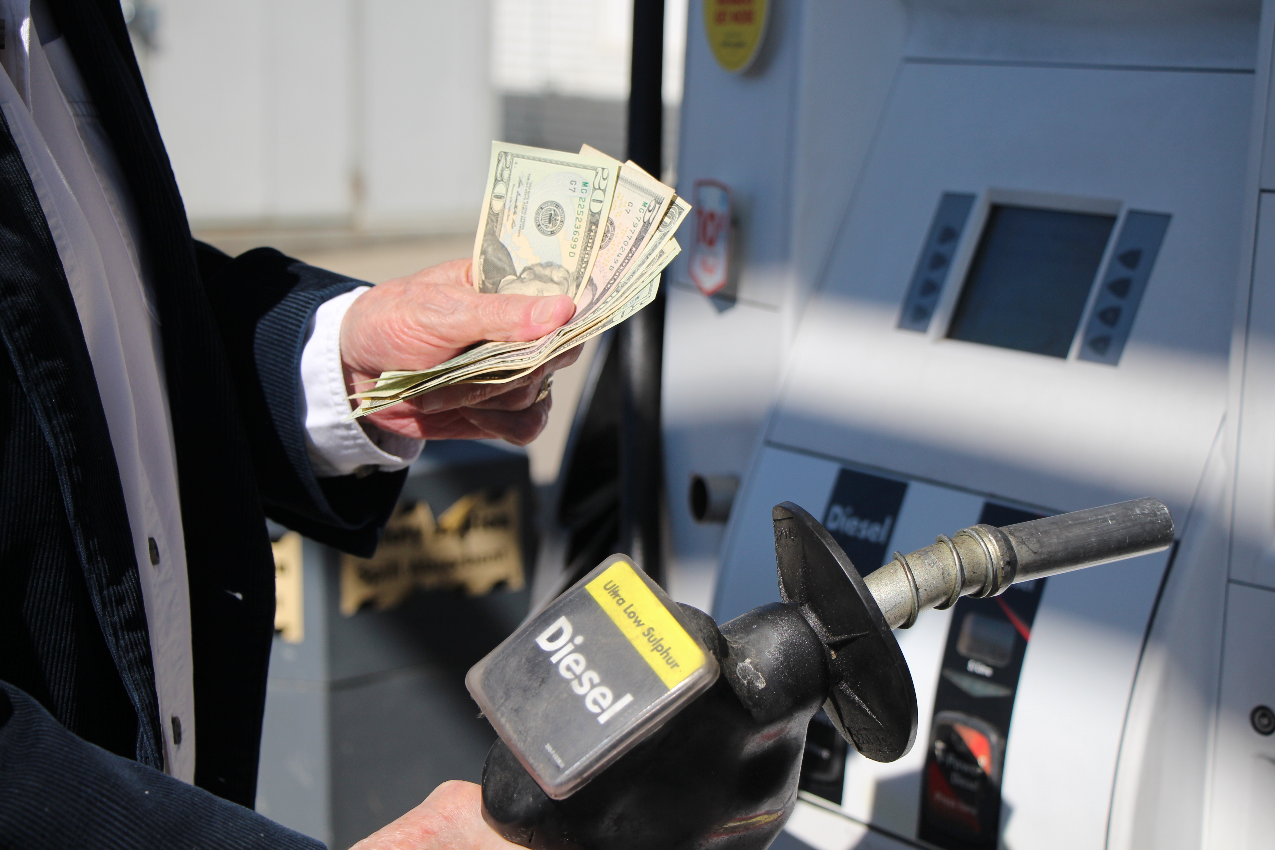 A man holds a stack of bills at a gas pump.